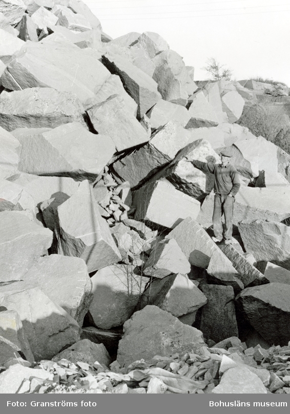 En man står bland stenblock i stenbrottet på Rixö