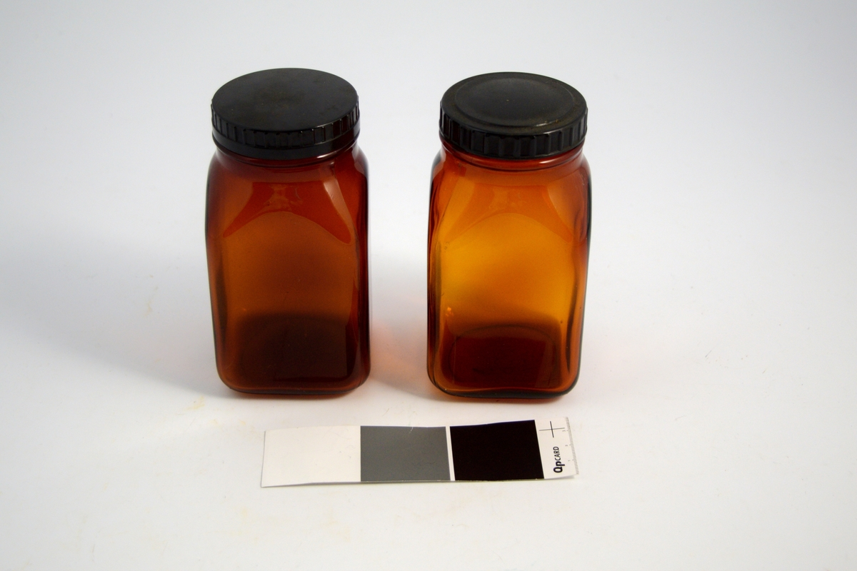 2 stk. brune firkantede glass med bakelittlokk. Glassene ble brukt til oppbevaring av tabletter produsert på apoteket.