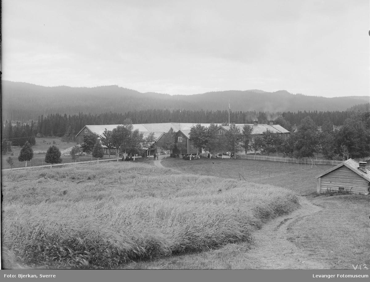 Garnes gård sett fra øst med løe og kornåker i forgrunnen.
