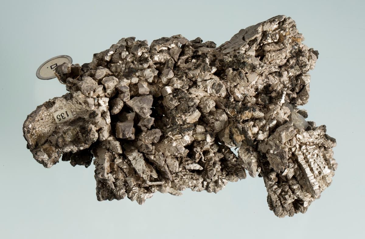 """Vekt 1263,11 g Størrelse: 15 x 9,5 x 4,5 cm Fra liste for Verdensutillingen i New York i 1938: """"6. Krystallklase av gedigent sølv, lamellære tvillingkrystaller. Opptrer i kalkspat."""" Nr. 291 i Størens katalog: """" Krystallgitter, spisse oktoeder i kalkspatt, paasittende smaa krystaller av magnetkis (hexagonale søiler) Nr. 2 fra Størens (?) rammer: Gitterkrystaller av kvikksølvholdig gedigent sølv med påsittende krystaller av magnetkis."""