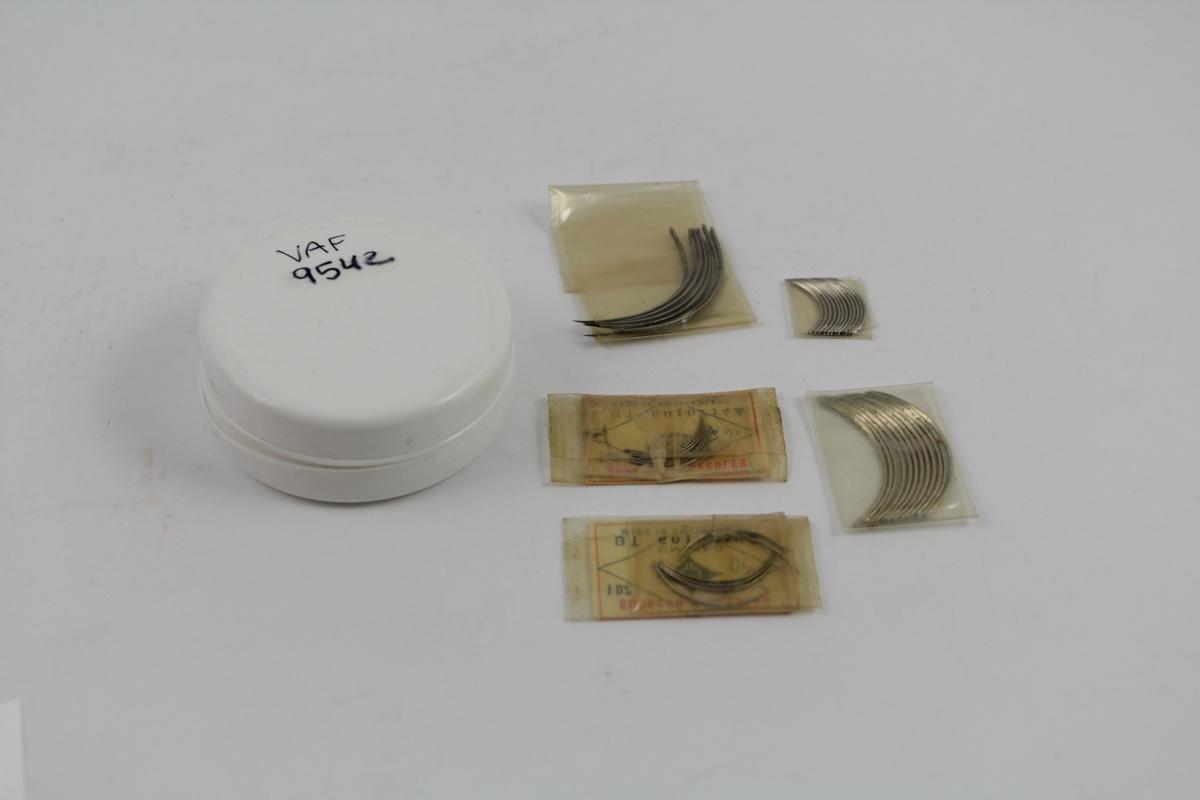 Plastsalveeske fylt med suturnåler. Krumme nåler, ulike størrelser. 4 plastpakninger i sirkulær plasteske. Ble solgt fra apotek. Skulle brukes til sying av operasjonssår med sutursilke, alt skulle være sterilt.