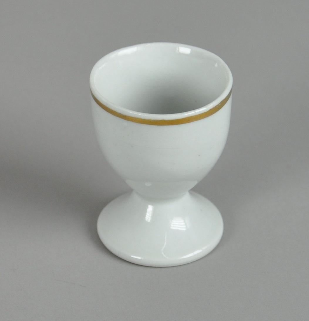 Eggeglass av glassert keramikk, med stett. Ved munningsranden er det en påmalt stripe i gullfarge.
