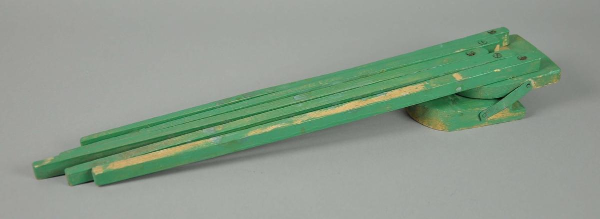 Tørkestativ av tre, malt grønn. Har fem utbrettbare stenger, montert med skrue.