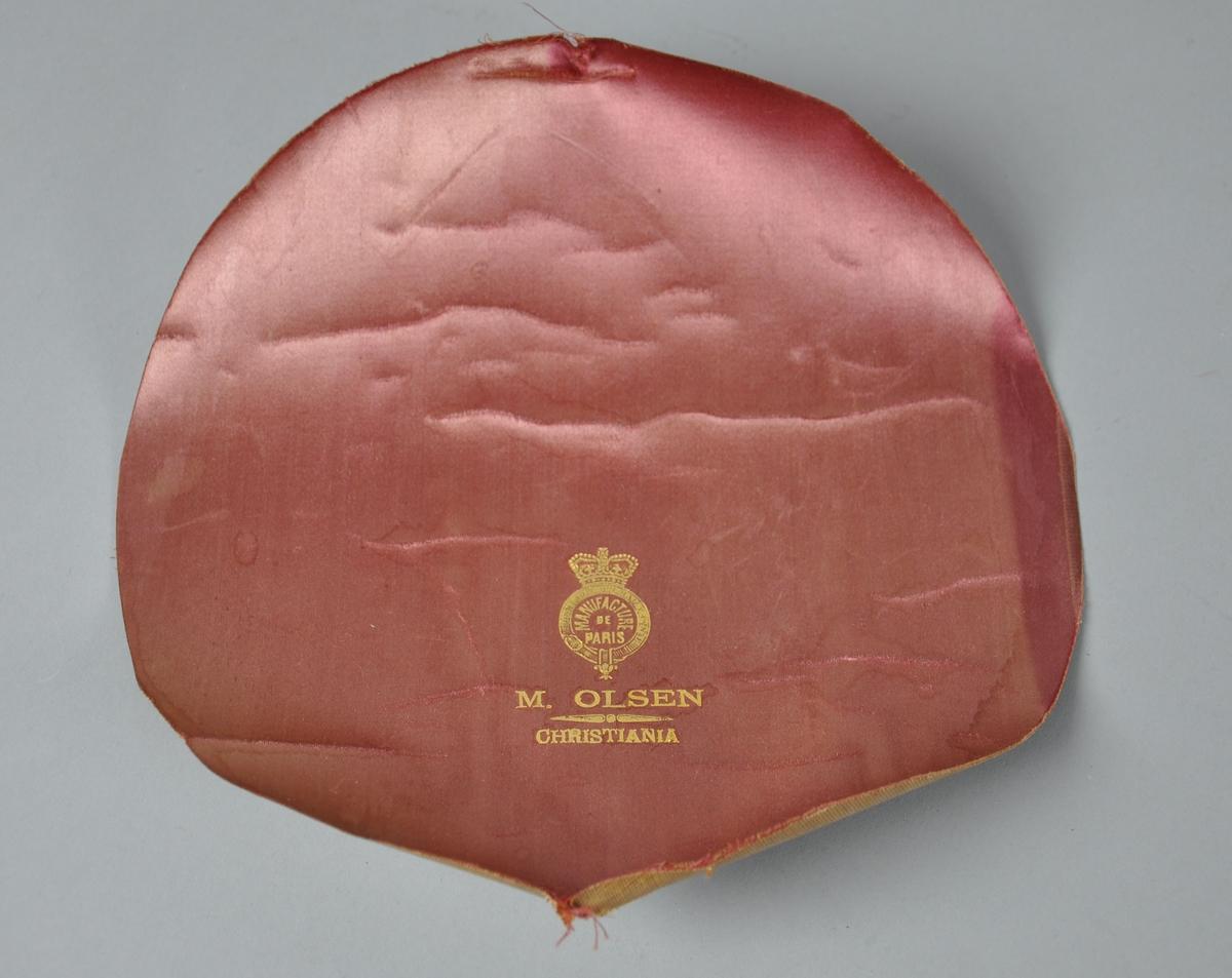 Rundt hattefor av rød silke. Stoffet har merker etter bretting.