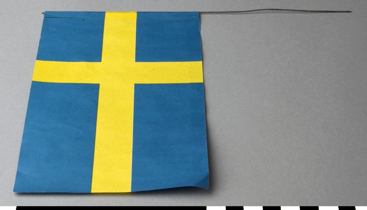 Flagga av papper, svensk. Flaggan är limmad på en ståltråd, som är avsedd att stickas fast i en gren. Trådens längd/höjd: c:a 220 mm.