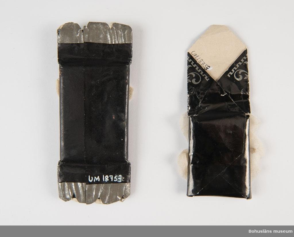 Två stycken svarta begravningskarameller. Papp med tyllrosett. Skilda motiv på bokmärken som dekoration mitt på.