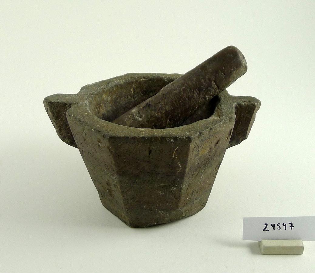 8-kantig mortel i kalksten med ornerade sidor. Stöt av samma sten.