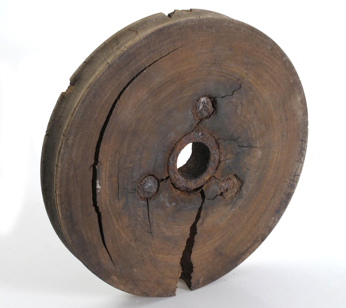 Blokkskive. Pukkenholt og jern. Rund skive med hull i midten, utforet med bøssing av støpejern. Ytre kant konkav. Tilstand juli 1977: Jernet rusta, sprukket skive.