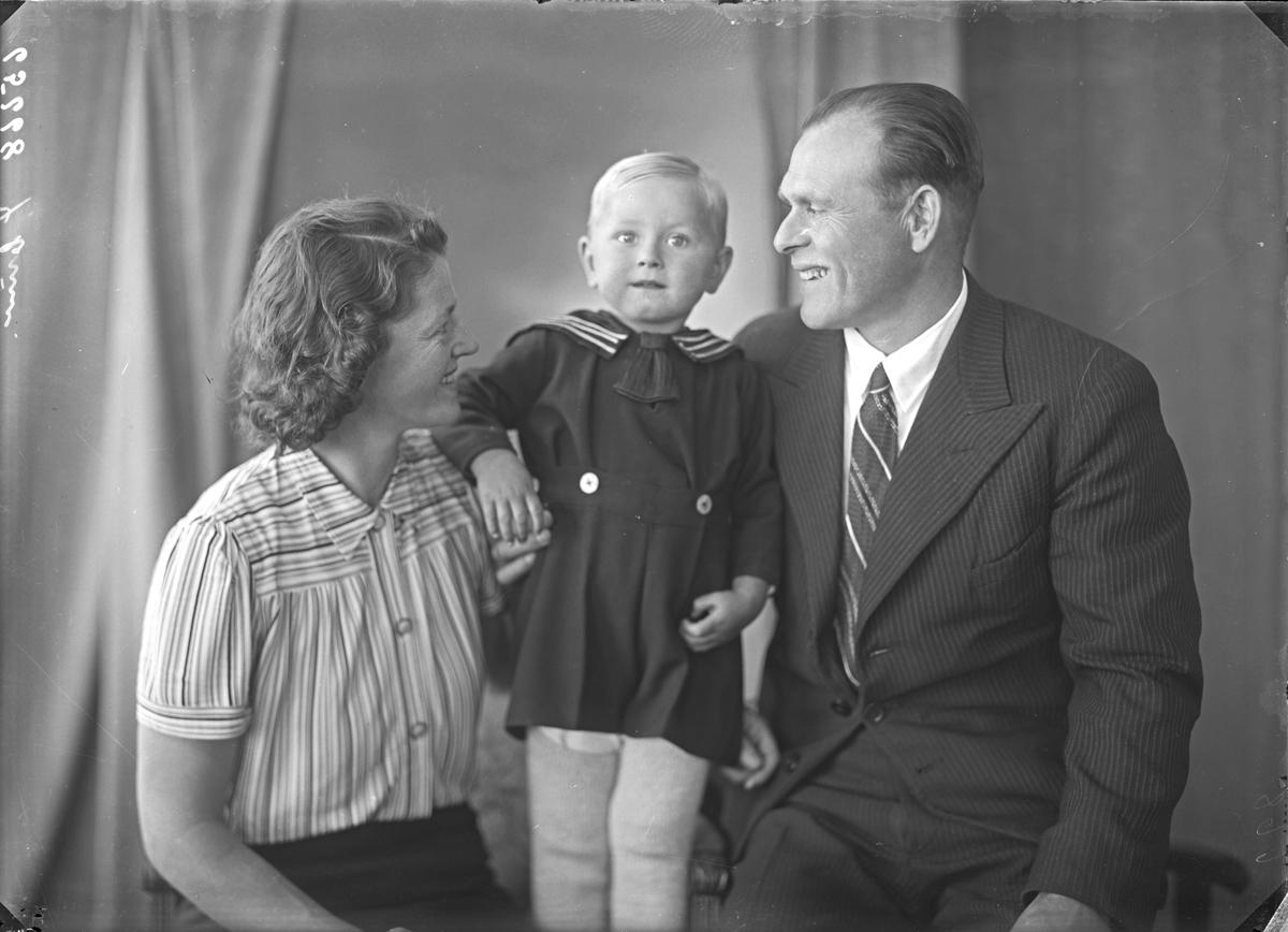 Portrett. Familiegruppe på tre. Ung kvinne, ung mann og en ung gutt. Bestilt av Odne Olsen. Aksnes.