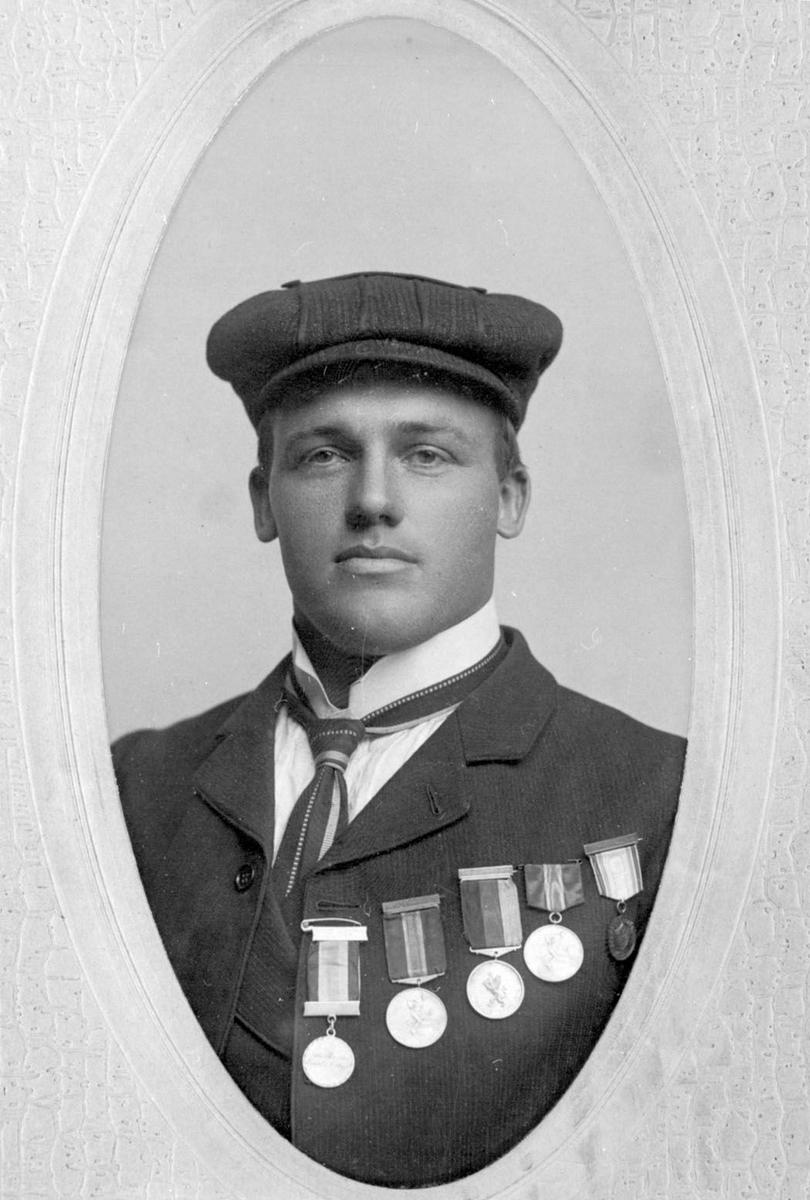 Ovalt brystbilde av Knut G. Helland i Amerika. Han har fem skimedaljer på brystet.