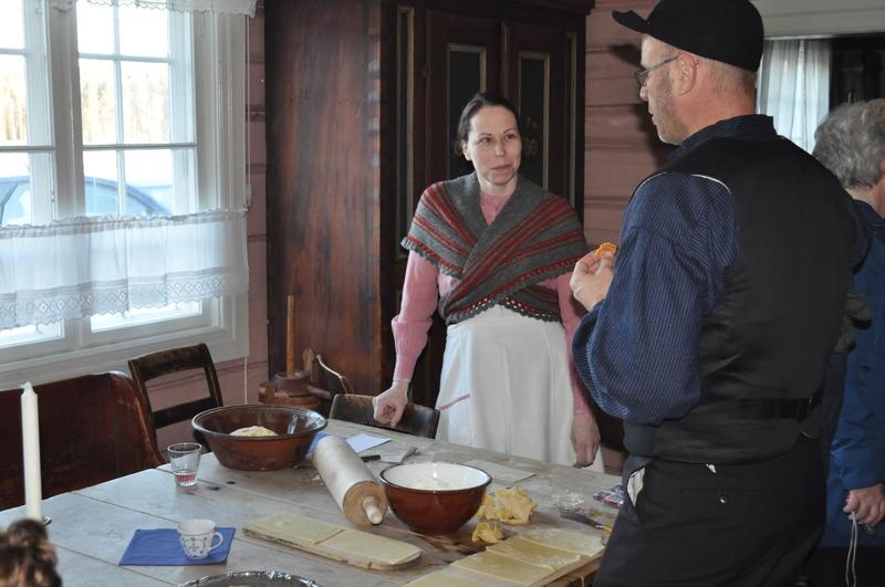 Kristin Hove deler ut smaksprøver på nystekte goro til museumsbestyrer Knut Ola B. Storbråten i kjøkkenet i Gjersøyenbygningen på Odalstunet under Jul i stuene i 2017.