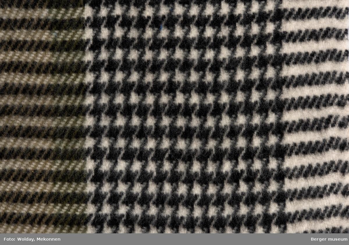 Prøvestykke med tre felt; pepitamønstret midtfelt, med stripefelt på hver side av det, det ene i grønt og sort-hvitt, de to andre i sort og hvitt. Det er klippet et lite stykke av det grønne feltet. Kåpe, bekledning Trolig kvalitet 5784 - se BMF.03198-C1 og C2 Melert, litt pepita-aktig
