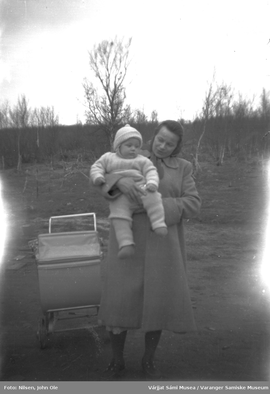 Berit Hansen holder sønnen sin Øystein. Ved siden av henne står barnevognen, trær i bakgrunnen. Fuoitnjárga / Bunes i 1952/53.