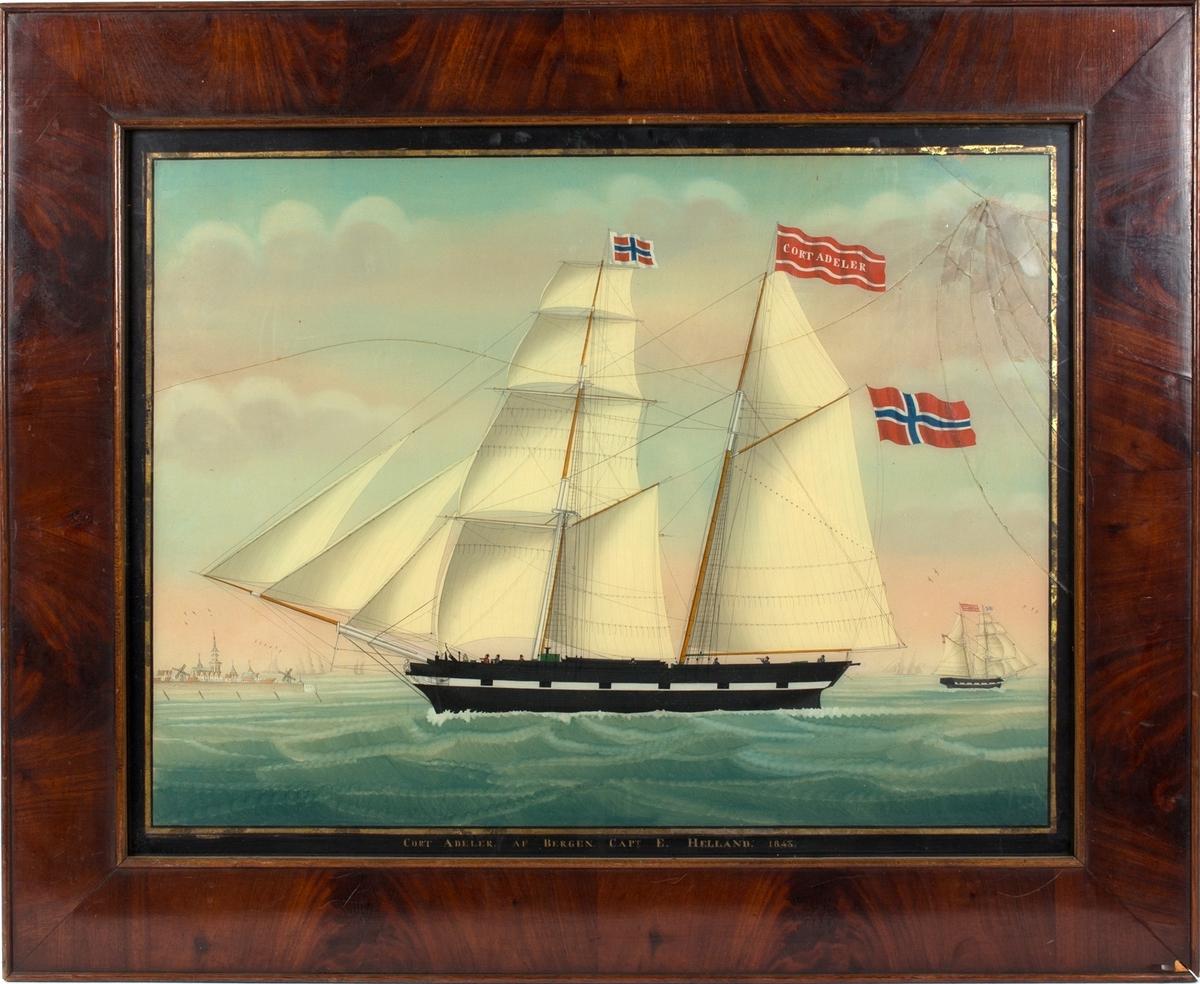 Skipsbilde av skonnertbrigg CORT ADELER fra Bergen. Skipet under fulle seil utenfor Vlissingen, Nederland (til venstre i motivet). I framre mast og akterste mast norske flagg, i toppen av aktermasten vimpel med skipets navn. Mindre skip i bakgrunnen. Syv mann på dekk.