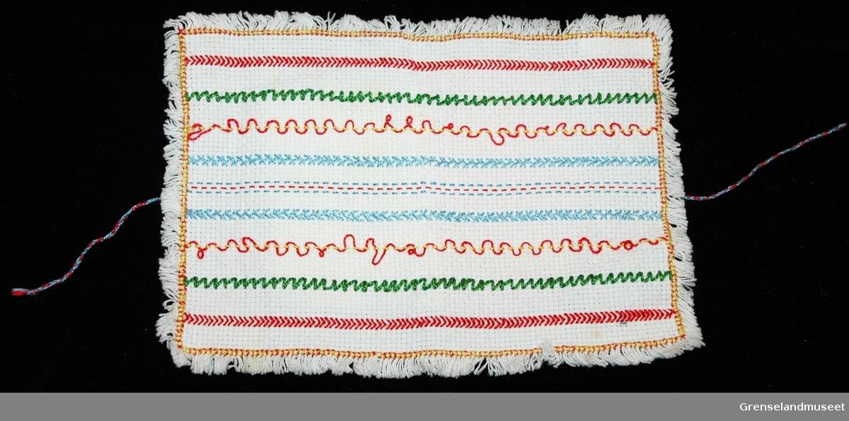 Nålebrev av type som ble laget i håndarbeidsundervisning på 1950-tallet. Ytterdel i aidastoff med tellesømsbroderi. Tvunnete snorer til sammenknytning. Innerdel utgjør selve nålebrevet, strikkete lapper i bomull i rødt og gult. Sitter trre synåler i nålebrevet