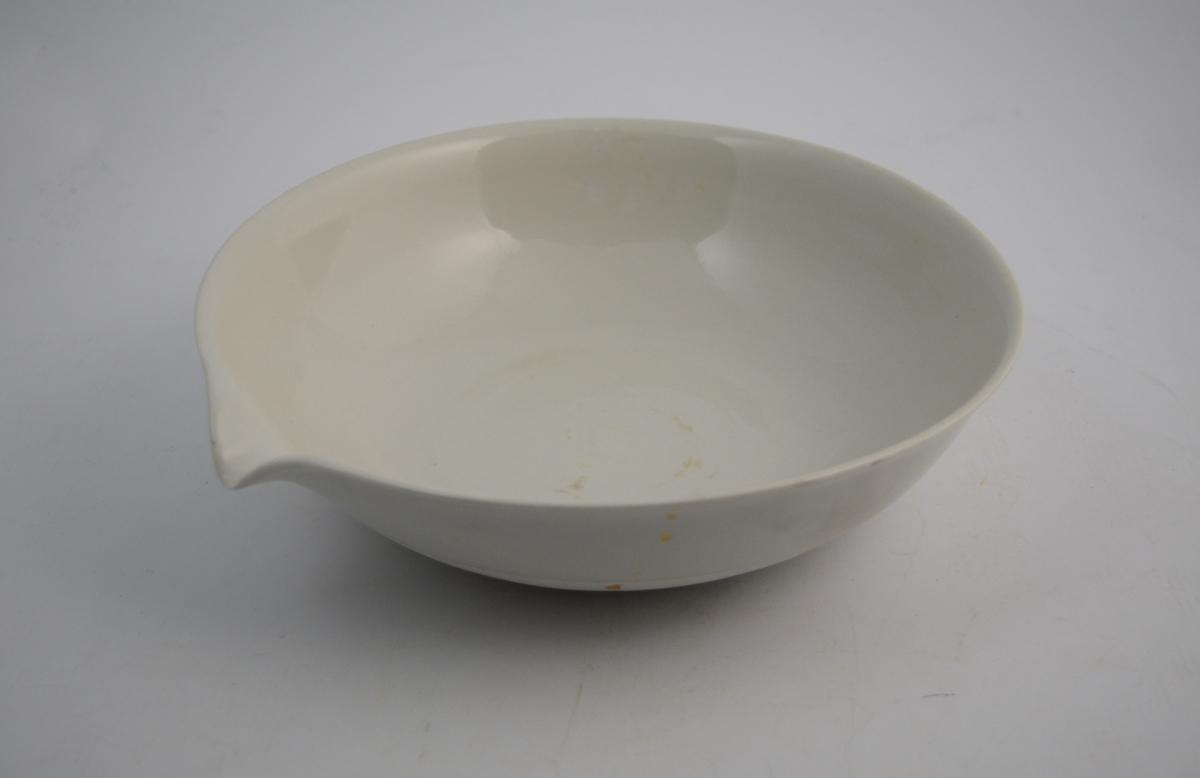 Sirkelformet hvit porselensskål med helletut. Glasert inni og ca. 5 cm fra kanten utenpå - resten utenpå er uglassert. Skålen ble brukt til produksjon av legemidler, kanskje på vannbad.