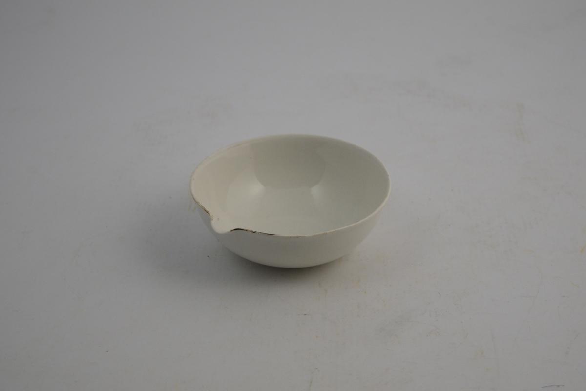 Sirkelformet hvit porselensskål med helle tut. Ca. 150 ml. Glasert inni og utenpå. Skålen ble brukt til produksjon av legemidler på laboratoriet på apotek.