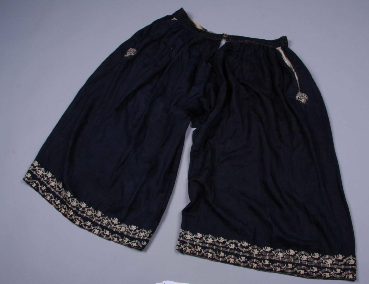 Av mørkeblå silke med mønster i samme farge. Benklærne er sydd sammen av to stykker med en innfelt firkant mellom benene, 24 x 24 cm. De er oppsplittet foran og bak ovenfor innfellingen med belegg 9 cm. nedover. Oventil er de rynket til en linning av samme stoff, fôret med grov, hvit lin. Linningen snøres sammen bak. Foran har benklærne antagelig vært knyttet sammen med bånd, nå defekt. Det er pyntestikninger og små kryss øverst i kanten på linningen av gulhvitt lingarn. I hver side er det åpning til en lang, spiss lomme av hvitt linstoff. Rundt åpningen samme pynt som på linningen samt en blomst nederst sydd i plattsøm og silkesting. De lange, rette, vide ben avsluttes nederst med en fall og broderte blomsterranker. Små kryss nederst i kanten.