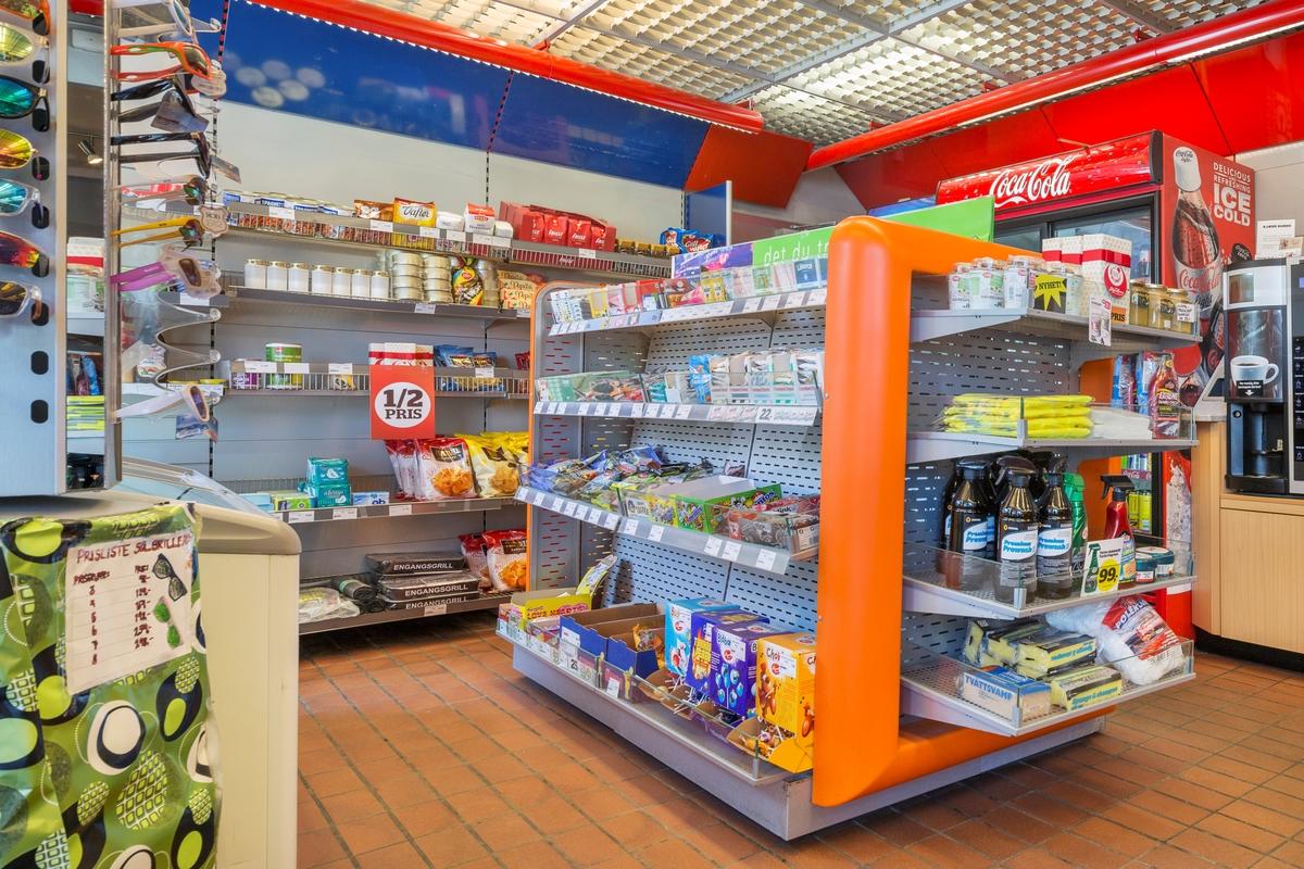 Statoil Hemnes. Butikk interiør med hylleseksjon med sjokolader, dagligvarer og bilpleiemidler. I bakgrunnen vegghyller med dagligvarer.