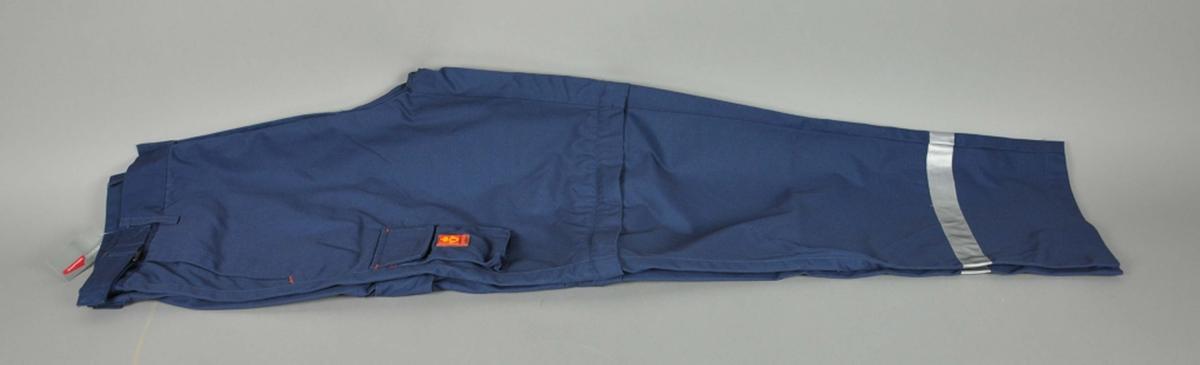 """Mørekblå uniformsbukse av typen """"Zipoff"""". Postlogo. 5 lommer og mobillomme. Refleksbånd nederst på begge ben."""