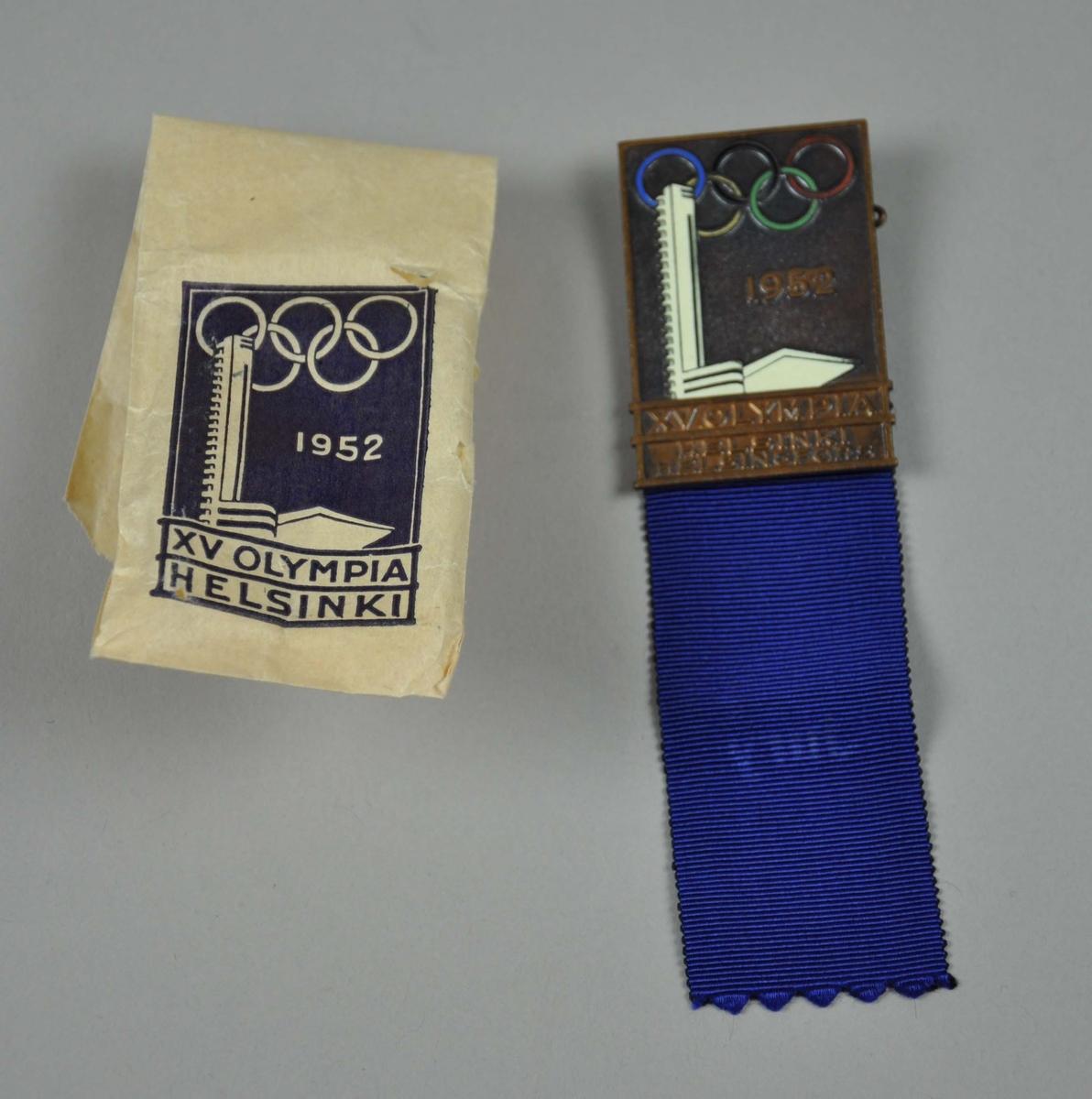 Emaljert badge med de olympiske ringer i korrekte farver. Siluetten av Olympiatårnet  i hvitt og årstallet 1952. Nederst på metallet kommer innskriften :XV OLYMPIA HELSINKI  HELSINGFORS.Blått bånd er festet i binders bak på badgen,påtrykk: Jury. Badgen ligger i hvit original papirpose med identisk påtrykk i blått.