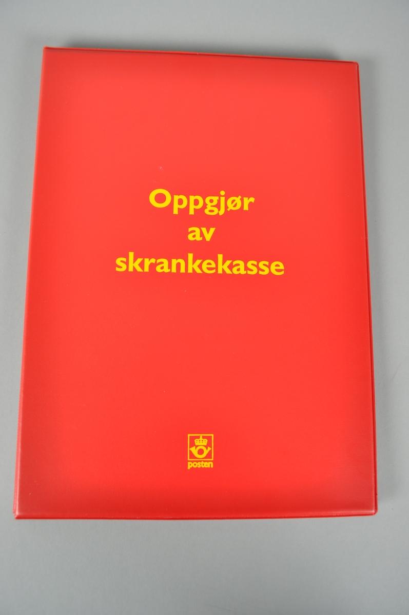 Rød oppbevaringsperm for oppgjør med gul påskrift.