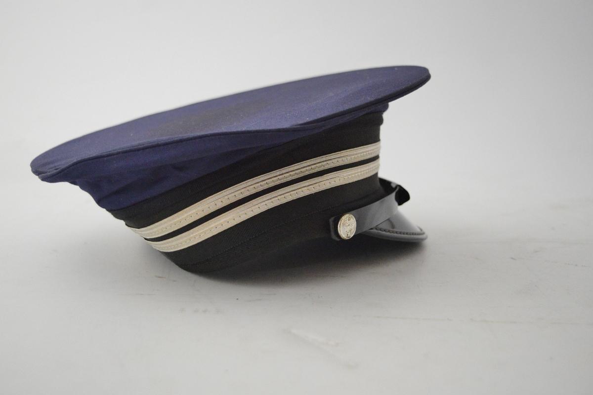 Lokomotivførerlue i mørkeblå og sort tekstil. To sølvfargede striper, og rød, hvit, blå rosett. Vingehjul mangler. Hakereim festet med små blanke knapper preget med løvemotiv. Blank sort brem.