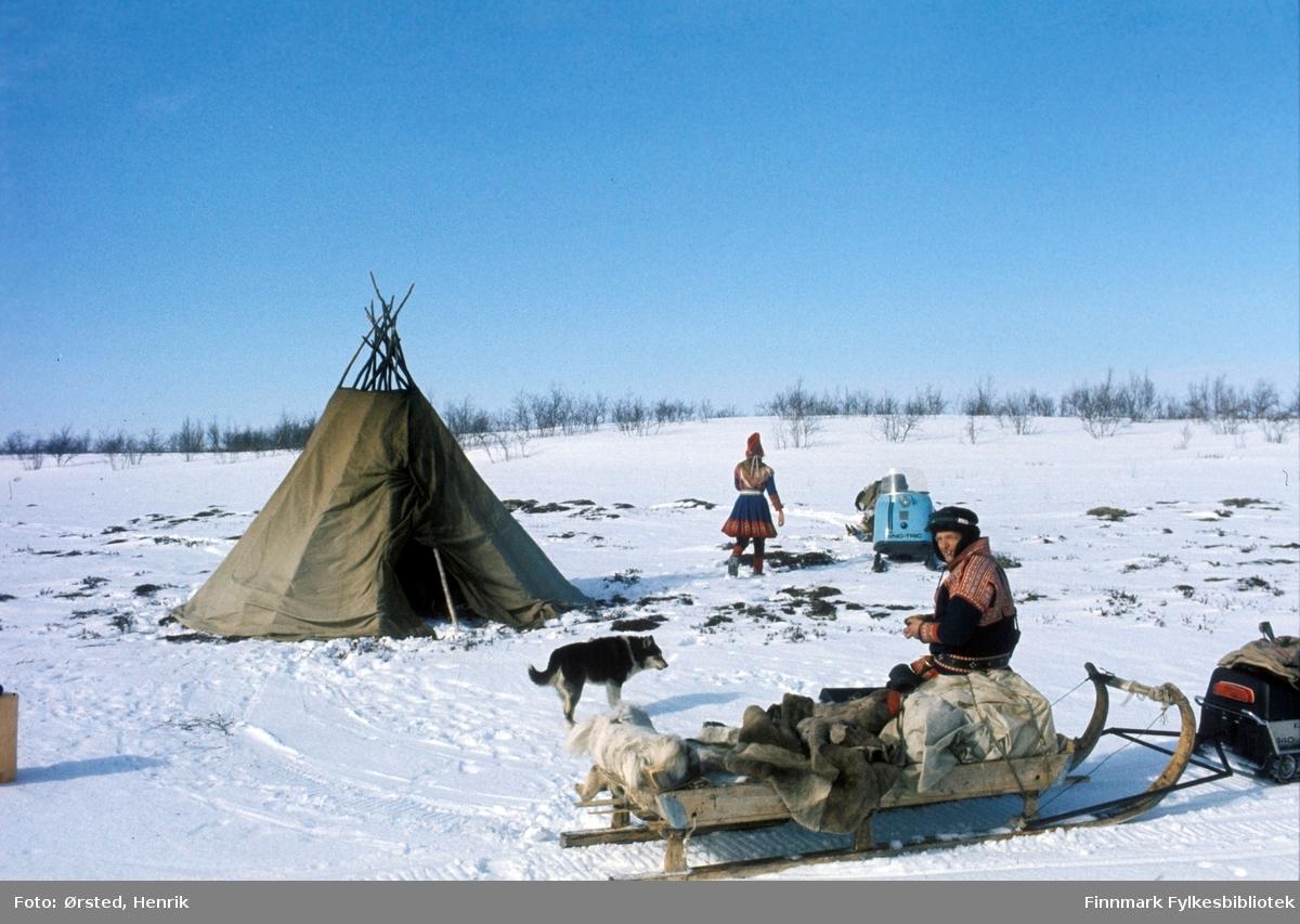 """Postfører Mathis Mathisen Buljo, bedre kjent som """"Post-Mathis"""" i samiske kretser, har kommet frem til et stopp på postruta og sitter på skuteren i solskinnet.   Fotograf Henrik Ørsteds bilder er tatt langs den 30 mil lange postruta som strakk seg fra Mieronjavre poståpneri til Náhpolsáiva, videre til Bavtajohka, innover til øvre Anárjohka nasjonalpark som grenser til Finland – og ruta dekket nærmere 30 reindriftsenheter. Ørsted fulgte «Post-Mathis», Mathis Mathisen Buljo som dekket et imponerende område med omtrent 30.000 dyr og reingjetere som stadig var ute i terrenget og i forflytning. Dette var landets lengste postrute og postlevering under krevende vær- og føreforhold var beregnet til 2 dager. Bildene gir et unikt innblikk i samisk reindriftskultur på 1970-tallet. Fotograf Henrik Ørsted har donert ca. 1800 negativer og lysbilder til Finnmark Fylkesbibliotek i 2010."""