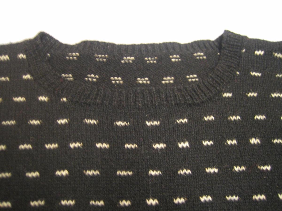 Tröja slätstickad i svart ullgarn och ränder i flamgarn. Ärmarna är isydda med rak insättning mot axeln.  Halskanten, nederkanten och ärmmuddar är stickad i resårstickning.