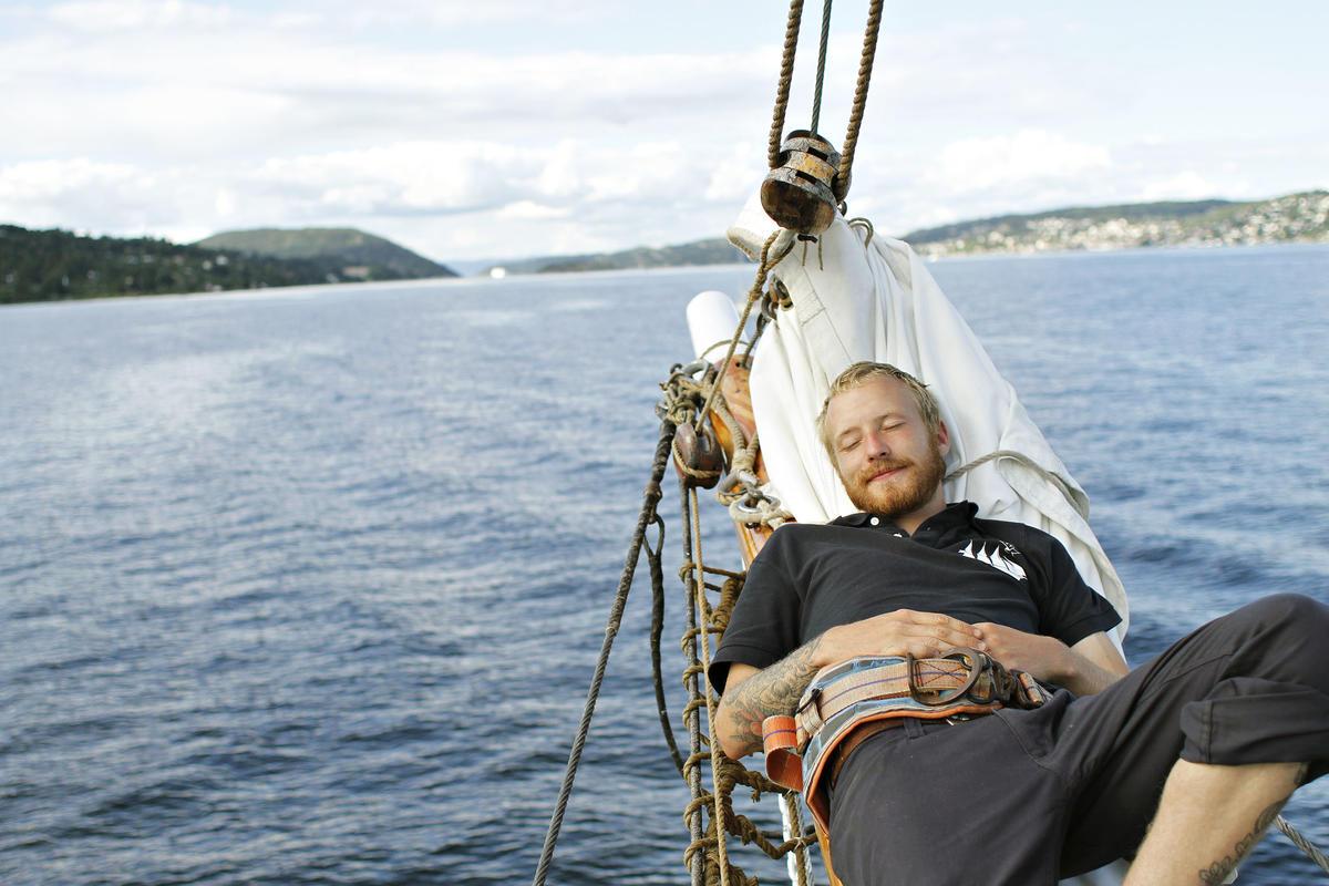 """Mann slapper av ombord skonnerten """"Svanen"""", blått vann, land og klar himmel i bakgrunnen."""