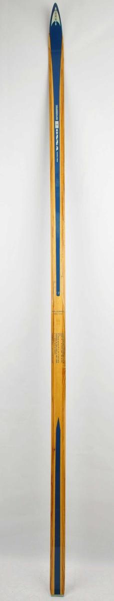Langrennski laga av tre. Lakkera trekvit overflate med blå dekorstriper oppå og på kvar side ved bindingsfeste. Metallbeslag bakre tupp. Bonna-emblem på framtupp.