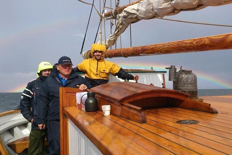 """Tre menn på dekk på skonnerten """"Svanen"""". Grå himmel og regnbue i bakgrunnen."""