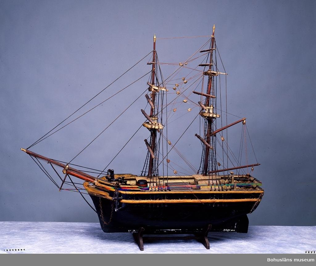 Ur handskrivna katalogen 1957-1958: Modell av segelfartyg - Brigg - L. (utom bogsprötet) c:a 69 cm. Skrovet grönmålat. Miniatyrtunna medföljer modellen. Föremålet relativt helt. Uddevalla.