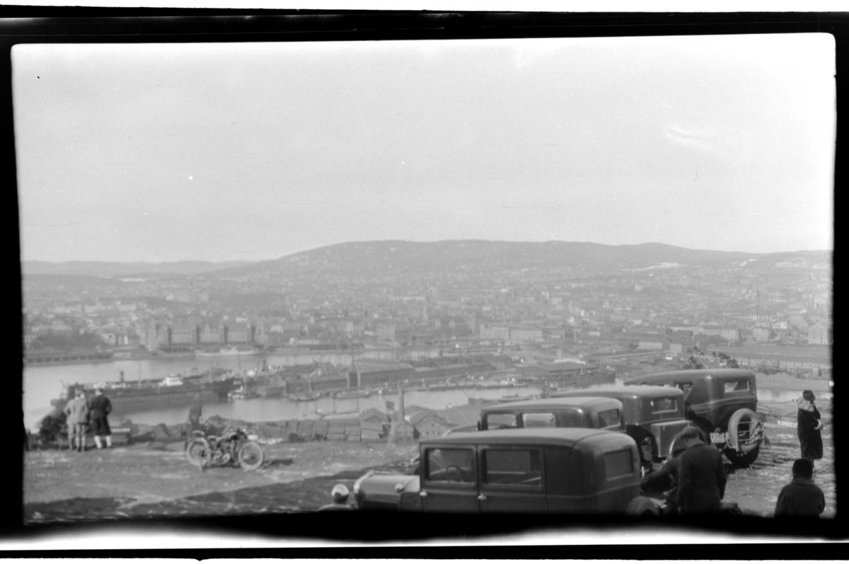 Flere biler står parkert på Ekeberg med utsikt mot Oslo. Fotografert 1930.