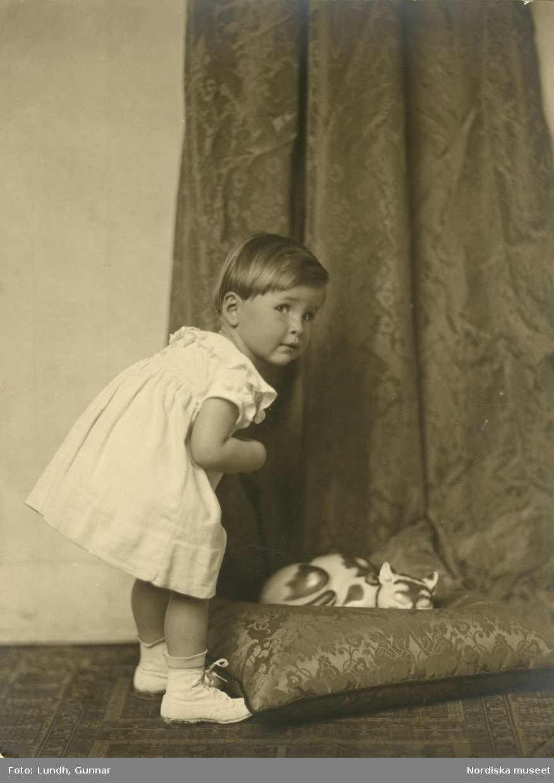 Porträtt av flicka, bredvid henne en keramikkatt på kudde. Varuhuset Wertheims porträttateljé, Berlin.