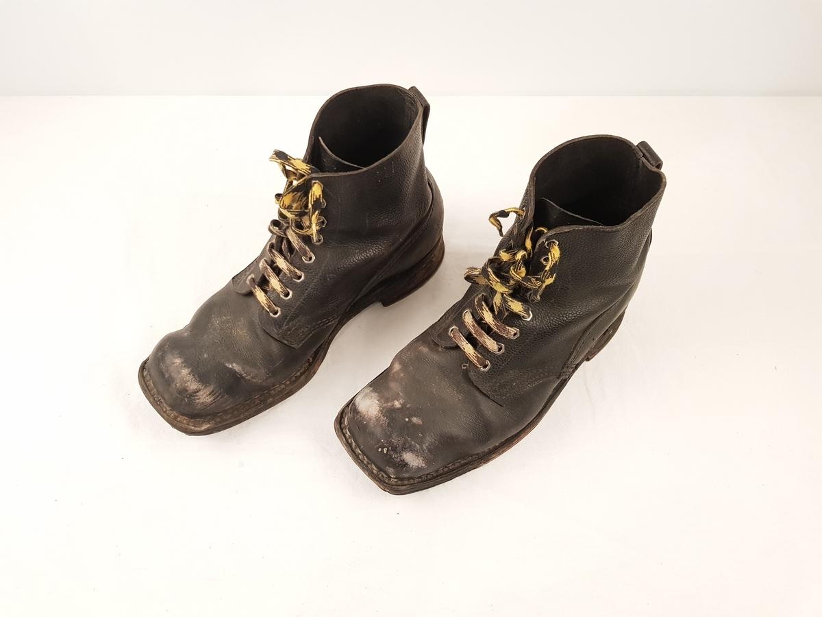 Svarte sko i lær med gul og svart snøring.