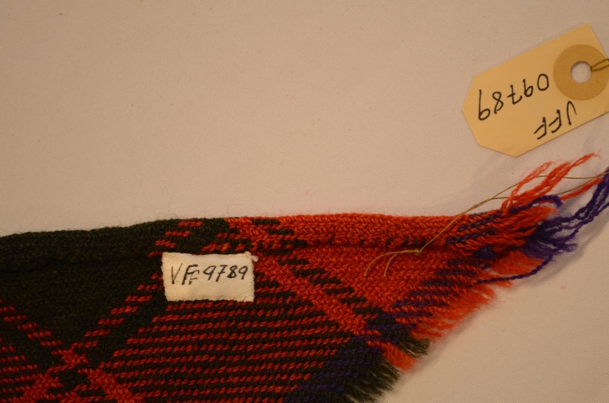 Sjal, trekanta ruta ullsjal, vove i kypert i raudt, svart, kvitt og fiolett. Falda for hand på langsida, små frynser på kortsidene. Samansett av to stykker.