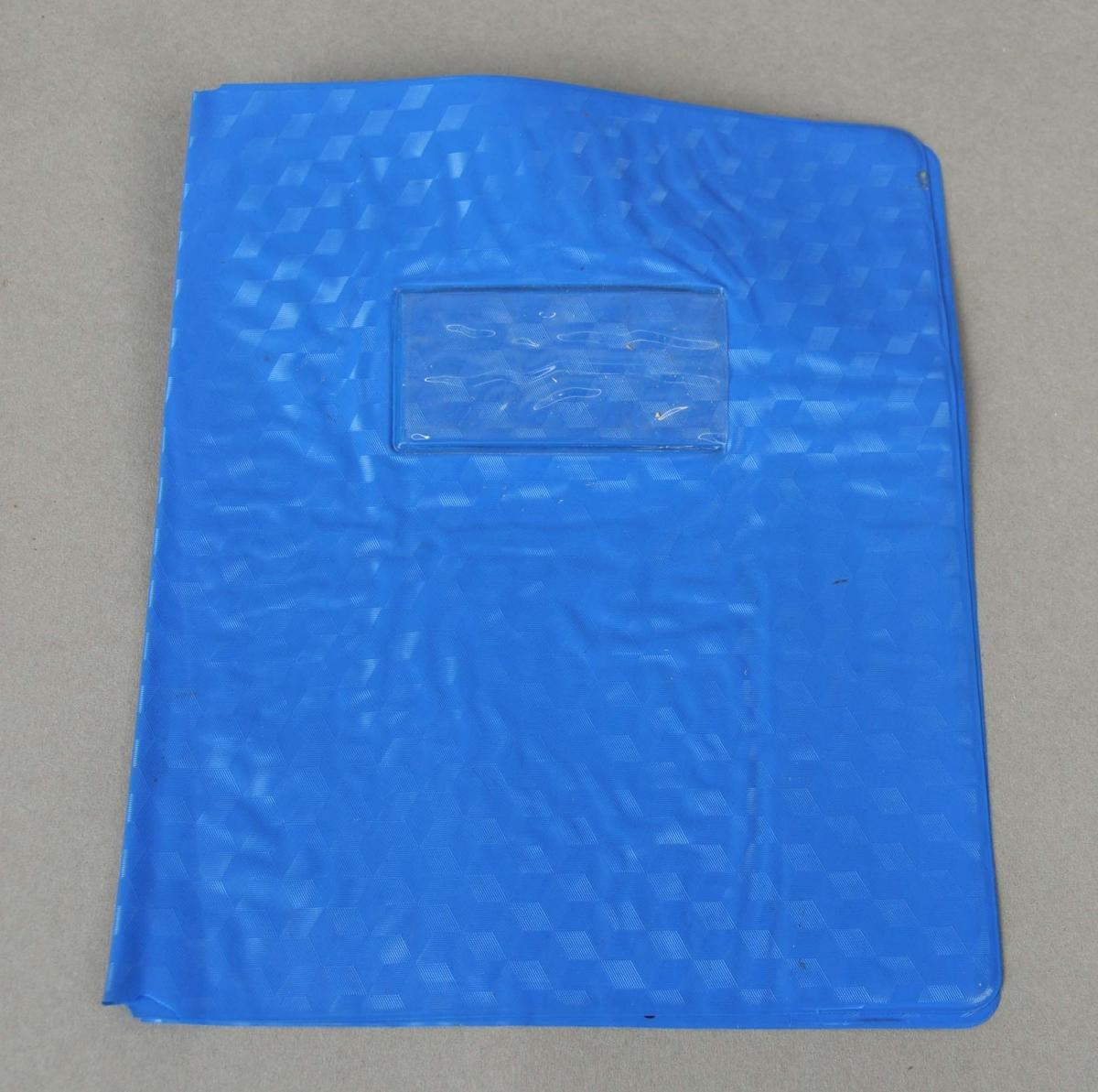 Bokbind i blå plast. Truleg til ei kladdebok/skrivebok (A5 format). Lomme av klar  plast på framsida til å stikke ein merkelapp inn i.