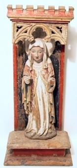 Stående kvinnligt helgon i skåp. Helgonet har ett dok på huvudet och är klädd i en vit, fotsid tunika och en röd mantel med förgyllda kanter och blått foder. Skåpet har sockel och baldakin med krön och genombrutet masverk.