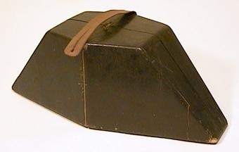 Hattfodral av trä, svartmålat utvändigt och klädd med brunt tyg invändigt. Askhalvorna hålles samman med två gångjärn nertill och med metallbeslag upptill. Ett bärhandtag av skinn är fastspikat upptill.