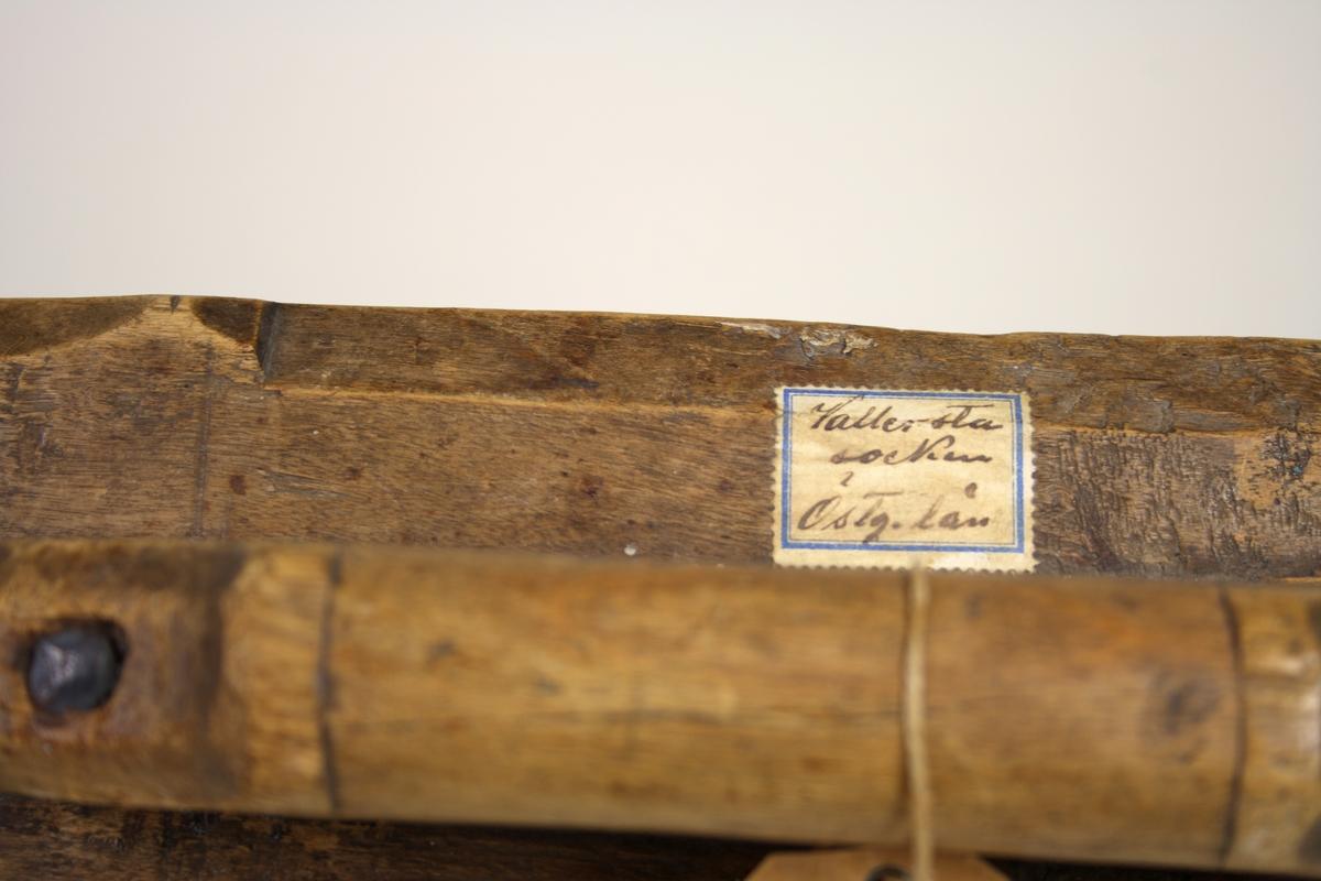 Mangelbräde med avfasade kanter och tvärgående band med uddsnitt. Handtaget inskjutet och förstärkt med järnspik.