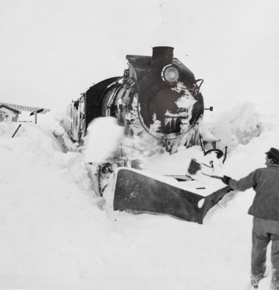 Toget fra Mo i Rana til Lønsdal har kjørt seg fast i snøen på Saltfjellet. Jernbanepersonalet arbeider med å spa løs toget. Damplokomotiv type 33c nr. 396.