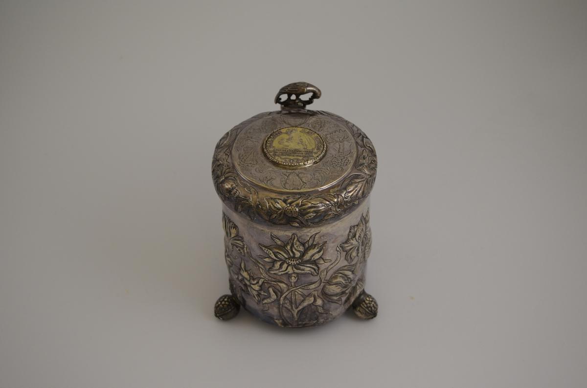 Sølvkanne med lokk i drevet sølv. Blomsterdekor. Mynt innfelt i lokket og fuglefigur som dekor på hengsel.