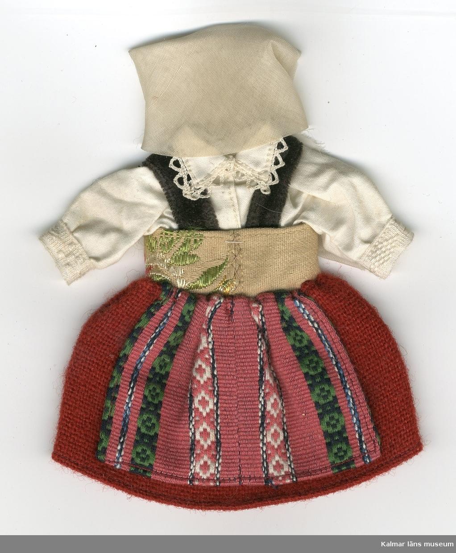 KLM 28082:3. Dockdräkt, dam, av textil, ylle, bomull och sammet. Dräkten består av kjol, förkläde, väst, skjorta och huvudbonad. Nationaldräkt från: Frosta, Malmö, Skåne.