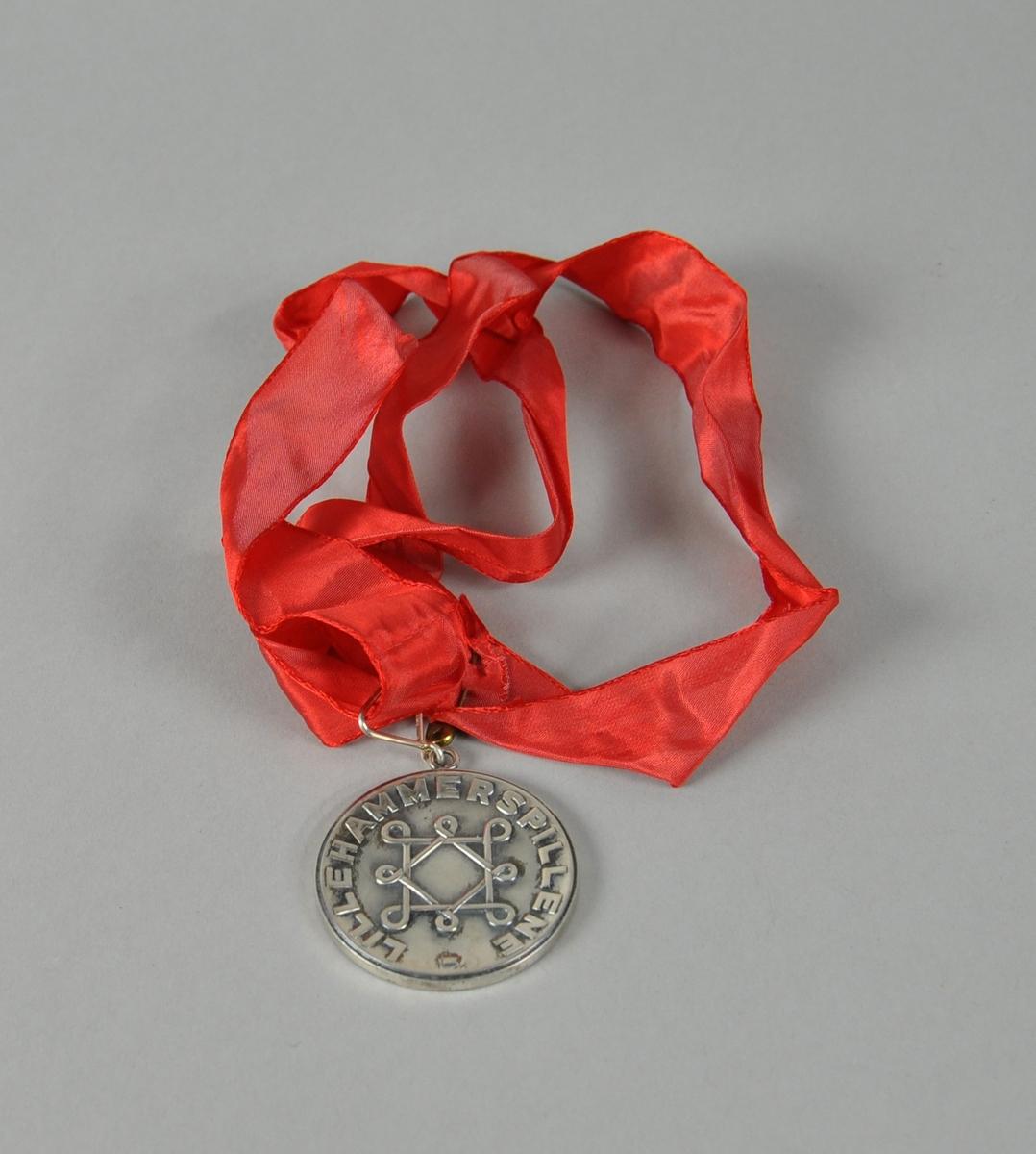 Rund bronsemedalje med rødt bånd, med symbol i sentrum og tekst rundt kanten.