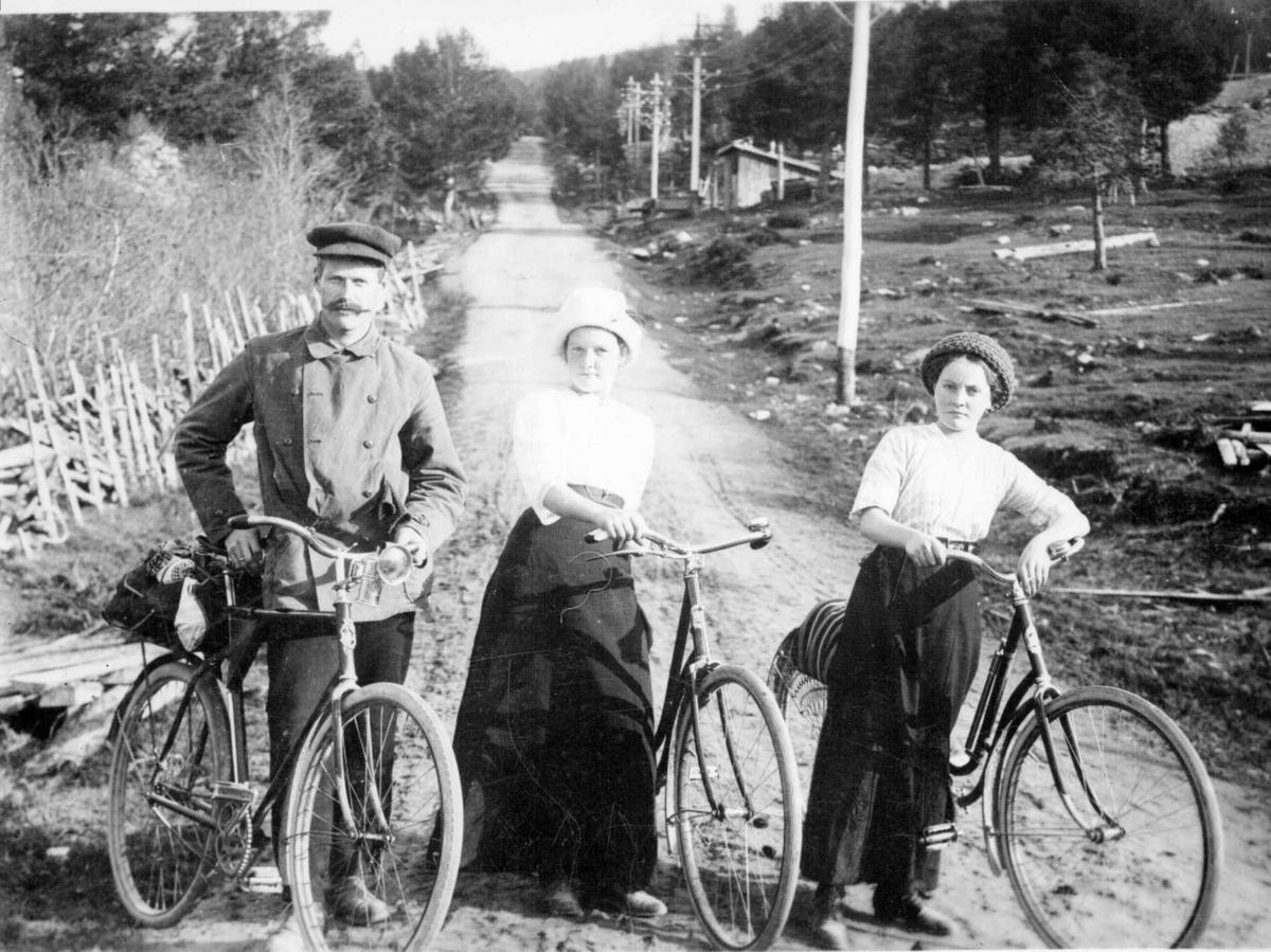 Repro: Syklister. To kvinner og en mann stående på en vei.