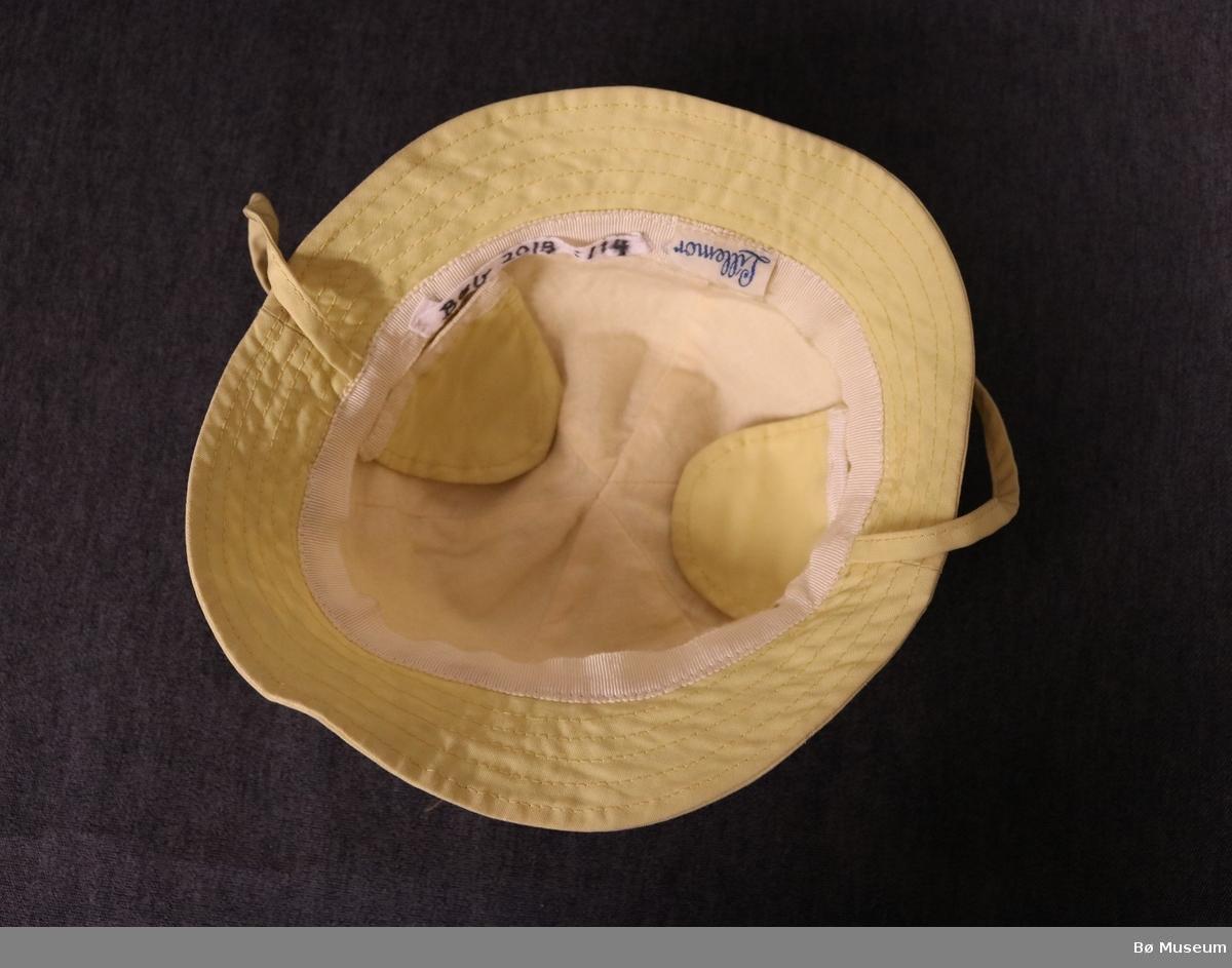 Hatt med brem til barn. Hatten har rund form, øyreklaffar og to snorer til å knyte under haka. Pullen er sydd saman av seks tøystykker.