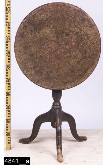 """Anmärkningar: Fällbord, Jacob Sjölin, 1767-1779.  Rund bordsskiva med profilerade kanter. Profilsvarvat ben. Tre S-formade fötter. Baktill finns stämplar som lyder """"KÖPINGS HALLSTÄMPEL"""" samt """"JAC. SIÖLIN. / KÖPING. No 315."""" (bild 4841__b). H:1080 Diam:610  Bordet går att fälla upp, höjden blir då 1080 mm. I nedfällt tillstånd är det 750 mm högt (bild 4841__c). Bordsskivan är fanerad med alrot, blindträet är furu. Alroten är fernissad. Benet och fötterna är av ljust lövträ och är svärtade. Bild 4841__d visar närbild på bordsskivan.  Mälardalen och framför allt städerna Arboga, Köping, Kungsör och Eskilstuna var under 1700-talets senare hälft och början av 1800-talet centrum för tillverkning av alrotsfanerade möbler och föremål. Här tillverkades bl.a. fällbord, byråar och olika sorters askar. Föremålen såldes inte bara inom mälardalen utan även till Stockholm och till andra länder. Det främsta namnet inom alrotsföremålsproduktionen är Jacob Sjölin (1737-1785). Alroten togs inte från alens rötter utan från stamansvällningar vid rötterna. I synnerhet vid Mälarens stränder har tillgången på detta sorts virke varit god. På slottet förvaras en kortkatalog, upprättad av f.d. antikvarie Carin Thorsén. Den upptar över 300 alrotsföremål tillhörande museer, privatpersoner etc.  Jacob Sjölin (1737-1785), gick i lära hos Jonas Nordling i Arboga. Sjölin blev mästare under hallrätten i Köping och Kungsör 1767 och kvarstod som mästare intill sin död 1785. Ungefär 2000 föremål tillverkades i hans verkstad. Sjölins speciella ytbehandling (fernissa) på möblerna gav dem en särskild glans och hållfasthet. Ingen mästare i Sverige har överträffat Sjölin i framställandet av alrotsfanerade möbler. Sjölin använde sig av tre olika brännstämplar, av Åke Nisbeth klassificerade som typ A, vilken är äldst men också använd under hela Sjölins livstid och även efter hans död, mellan 1785-1788 då verkstaden drevs av Sjölins änka. Typ B (använd t.o.m. 1779) och typ C (använd fr.o.m. 1780 t.o.m. 1788 då"""