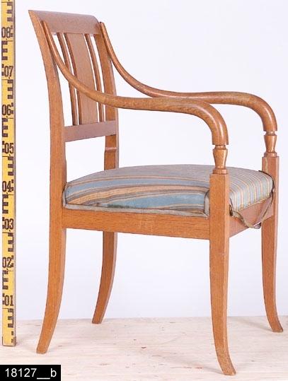 Anmärkningar: Karmstol, Karl Johan modell, 1900-tal.  Rakt överstycke. Svagt svängda bakstolpar. Genombruten rygg med en rektangulär ryggbricka och två ryggspjälor samt en ryggslå. Stoppad sits med randigt tyg. Svängda armstöd med balusterformade delar där benen tar vid. Samtliga ben är utåtsvängda från stolen (bild 18127__b). H:875 Br:590 Dj:535  Hela stolen är betsad.  Tillstånd: Höger armstöd är skadat och lagat. Sitsen är sliten.  Historik: Enligt kortkatalogen tillverkad av Sköld & Karlsson, Västerås. Gåva från Fröken Eva Karlssons, Västerås, dödsbo 1974 enligt testamente.