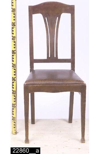 """Anmärkningar: Stol, senjugend, omkring 1920.  Pilbågeformat överstycke. Svagt svängda bakstolpar (bild 22680__b). Genombruten rygg med konturerad och genombruten ryggbricka. En ryggslå under ryggbrickan. Löstagbar stoppad sits med läderimiterande överdrag. Kontursågad framsarg. Två benslåar mellan bakbenen och frambenen. Frambenen har pyramidliknande fotavslutningar. H:960 Br:465 Dj:435  Hela stolen är betsad. Hela stolen är av ek utom sitsen som är av furu. Framsarg och sidosargar är delvis av furu.  Historik: Inköpt till utställning """" Bostad"""" hösten 1985 från Fastberg & Söner, Vångsta, Västerås för 125 kronor."""